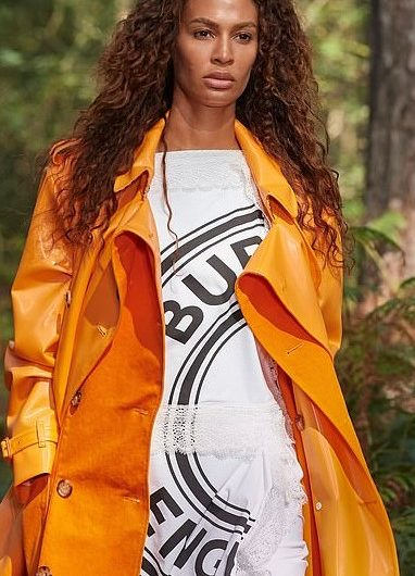 At the Virtual London Fashion Week show, Joan Smalls showed off her model figure in a bright orange burberry trench coat